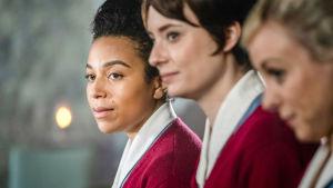 Kolme naista punaisissa paidoissa vierekkäin