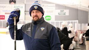 Jan-Peter Lassila, målvaktstränare i hockeyföreningen MUIK i Nykarleby, står med hockeyklubban invid sargen, redo att inleda kvällens träning.