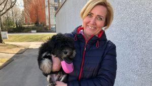 En kvinna med en hundvalp i famnen.