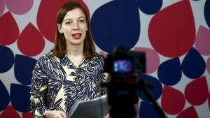 Li Anderson håller förstamaj-tal framför kamera med färggrann bakgrundsvägg.