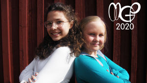 Isabel och Hilja står rygg mot rygg och ler mot kameran