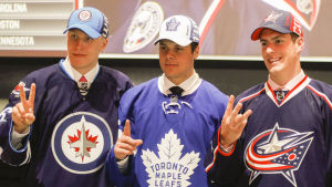 Tre unga ishockeylöften poserar i sina respektive klubbtröjor.
