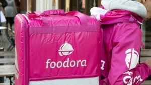 Foodora matbud med stor ljusröd väska med mat i går på gatan.