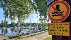 en förbudskylt mot simning fäst på en husvägg, intill en småbåtshamn