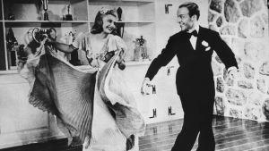 Ginger Rogers och Fred Astaire dansar och ser skrattande på varandra i filmen Swing Time.
