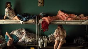 En sovsal där en fyra unga kvinnor sitter och ligger i sina sängar. Stillbild från filmen Eden.