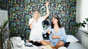 Malin och Siri sitter med pyjamas på i en obäddad säng. Malin står på knä och dricker skumppa, Siri fyller mera skumppa i sitt glas. Båda tittar in i kameran.