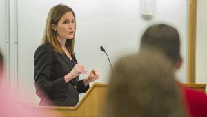 Amy Coney Barrett står vid ett podium och talar inför en publik.