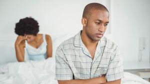 Man sitter på sängkant och ser irriterad ut, i bakgrunden en kvinna