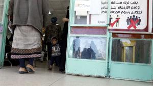 Ett barn står i dörren till en läkarmottagning i Jemen. Bredvid dörren finns en skylt som uppmanar besökarna att undvika folksamlingar