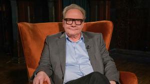 Mies (Jari Tervo) istuu nojatuolissa.