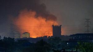 Brinnande fabriker och eldlågor slår upp mot himlen.