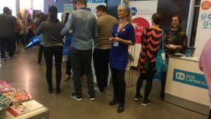 lång smal blond kvinna i blå åtsittande klänning och glasögon står bland folk på mässa i Logomo