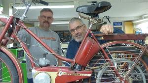 Två män tittar fram bakom en gammal röd moped. De befinner sig inne i en verkstad.