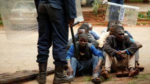 Kravallpolis ståd framför gripna demonstranter i Zimbabwes huvudstad Harare