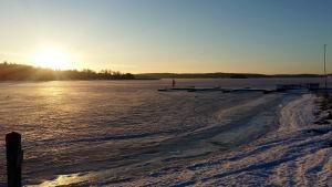 Solen lyser över isen och snöprydda bryggor en vinterdag.
