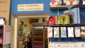 En bokhandel. Kvinna tittar på pennor. På väggen står en lapp: kontors- och skolmaterial.