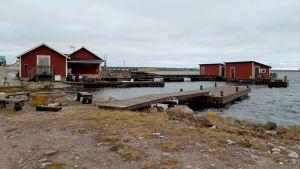 röda båthus vid en stenig hamn