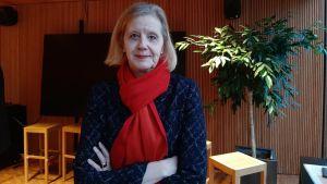 Katariina Salmela-Aro med blond page och röd halsduk. Står med armarna i kors framför en växt och en vägg.