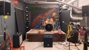 En träningslokal med en liten scen och instrument så som trummor.