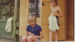 70-luvun valokuva, jossa kaksi nuorta poikaa märkätukkaisina rantasaunan terassilla.