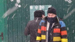 Två män vid en spegel utomhus i snöfall. En av dem vänder ryggen mot bilden.