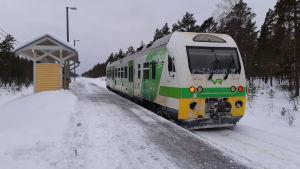 En grönvit rälsbuss på järnvägsspåret i Skogby.