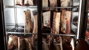 Nötkött som hänger på rad i ett torrskåp.