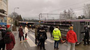 En grupp människor står och lägger upp stängsel vid järnvägen. Ett tåg kör förbi i bakgrunden. Det är mulet.