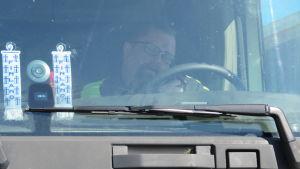En man sitter inne i en lastbilshytt. Han pratar i telefon och ser ner på papper. Bilen står stilla.