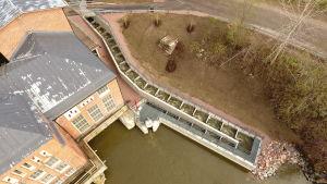 En bild på en fiskeväg som går längs en tegelbyggnad.
