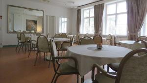 En matsal med stora fönster, stor spegel på ena väggen och flera mindre, runda bord med stolar runt borden.