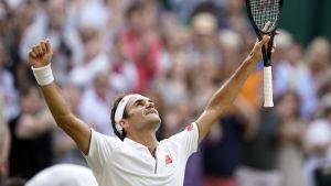Roger Federer lyfter händerna upp mot skyn.