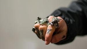 En hand som visar knogarna, tatuerade fingrar och ringar.