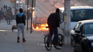 En bil brinner på en gata i Baltimore.