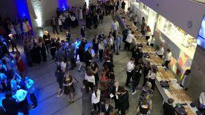 Elever står och minglar i mindre grupper i festsalen i Opinmäki skolcentrum. Det är feststämning.