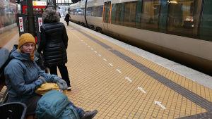 Sanna-Mari Kunttu, sitter på en tågperrong och väntar ikäldd mössa, jacka och vantar.