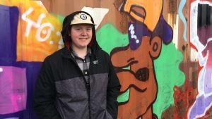 Jere Lindström värikkään graffitiseinän edessä