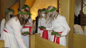 Tärnor inne i en kyrka, de har munskydd på sig. Förbereder sig, fixar bland annat med ljus och ljusmanschetter av lingonris.