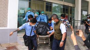 En bår med en liksäck förs bort från ett sjukhus i Myanmar.