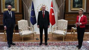 Europeiska rådets ordförande Charles Michel och kommissionens ordförande Ursula von der Leyen tillsammans med Turkiets president Erdogan. I bakgrunden syns EU:s och Turkiets flaggor, samt två stolar.