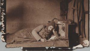 En soldat ligger och läser på sin fältbädd under första världskriget.