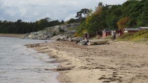 En sandstrand med båtar och fiskebodar.