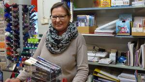 En kvinna står bakom en betjäningsdisk i en bokhandel.