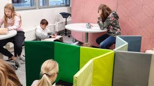 Elever jobbar på olika ställen i ett rum. Vissa sitter vid skrivbord, andra på golv.