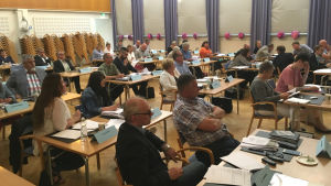 Ett fyrtiotal ledamöter sitter på möte.
