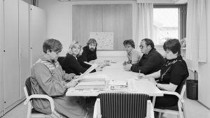Sex människor sitter vid ett bord.