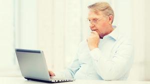 Äldre man använder en bärbar dator.