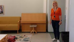 Blond långhårig kvinna i glasögon, orange blus och svarta byxor står vid ingången i ett rum med piano.