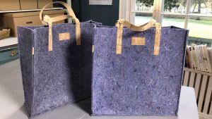 två väskor sydda av lumpfilt står på ett bord